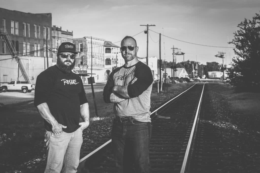 NATE AND BLAKE THE OWNERS OF ROGUE STANDING ON TRAIN TRACKS